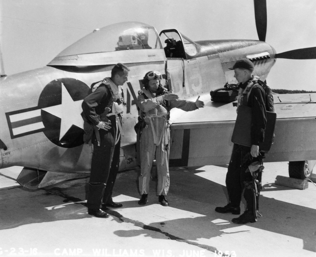 "U.S. Air Force personnel assigned to the 119th Fighter Wing""Happy Hooligans"", North Dakota Air National Guard, pose for a photo in front of a F-51D Mustang aircraft at Camp Williams, Wisconsin in 1953. Pictured left-to-right, Robert Olwin; Duane""Pappy""Larson; and Thornton E. Becklund. (A3604) (U.S. Air Force PHOTO) (Released)"