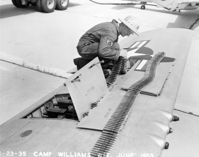 """A U.S. Air Force munitions handler assigned to the 119th Fighter Wing""""Happy Hooligans"""", North Dakota Air National Guard, loads .50 caliber ammunition into a F-51D Mustang aircraft, at Camp Williams, Wisconsin, in June 1953. (A3604) (U.S. Air Force PHOTO) (Released)"""