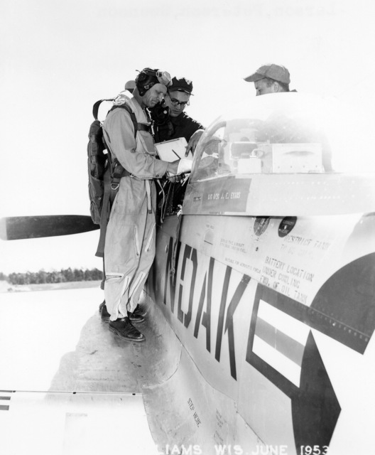 """U.S. Air Force North Dakota Air National Guard pilot Duane""""Pappy""""Larson (foreground left), signs his logbook with members of his ground crew, on the wing of a F-51D Mustang aircraft, at Camp Williams, Wisconsin, in June 1953. (A3604) (U.S. Air Force PHOTO) (Released)"""