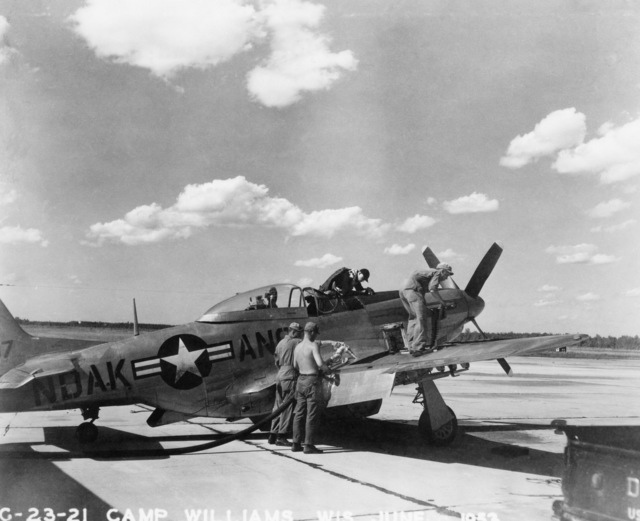 """U.S. Air Force personnel assigned to the 119th Fighter Wing""""Happy Hooligans"""", North Dakota Air National Guard, pose for a photo in front of a F-51D Mustang aircraft, at Camp Williams, Wisconsin in June 1953. L-R: Foster; Erickson; Becklund; and Knutson (A3604) (U.S. Air Force PHOTO) (Released)"""