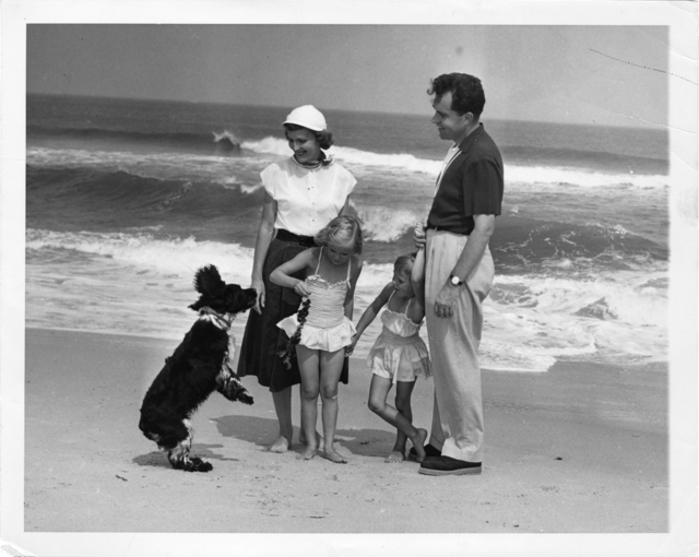 Richard, Pat, Julie, and Tricia at the beach in Mantoloking, New Jersey with their dog Checkers. Checkers stands on hind legs
