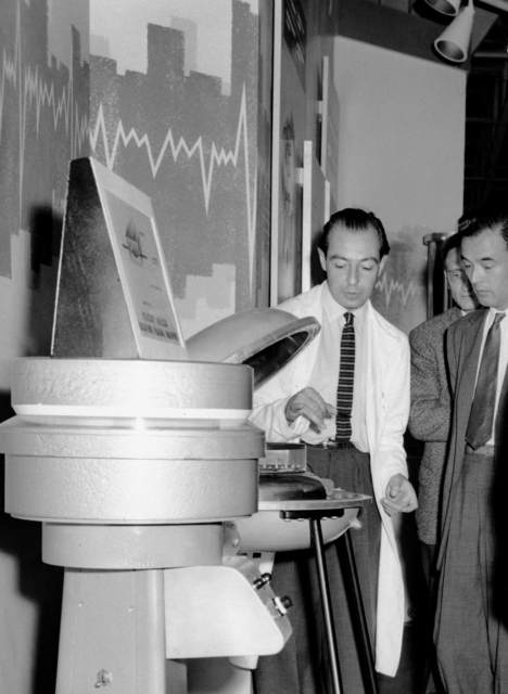 During the first International Conference on the Peaceful Uses of Atomic Energy in Geneva, Switzerland, Wulf Kunkel (Physics) explains to visitors a rotating-plasma device. In the foreground is the rotating-mercury analog. Morgue 1958-69 (P-3) [Photographer: Donald Cooksey]