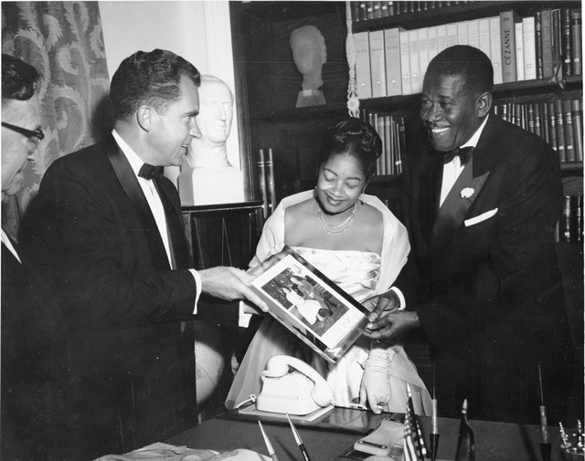 Vice President Richard Nixon presents a framed photograph of Dwight and Mamie Eisenhower to Haiti ruler Paul Magloire and his wife Yolette Leconte Magloire