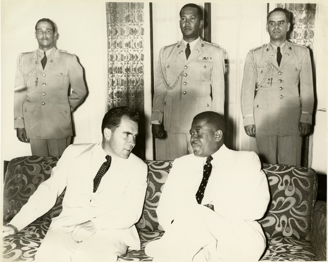 Vice President Richard Nixon seated with Paul Magloire during his trip to Haiti. Military personnel stand behind them