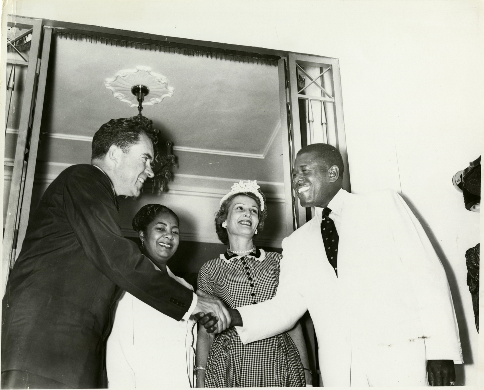 Vice President Richard Nixon shakes hands with Haiti rule Paul Magloire. Pat Nixon and Yolette Leconte Magloire stand behind them