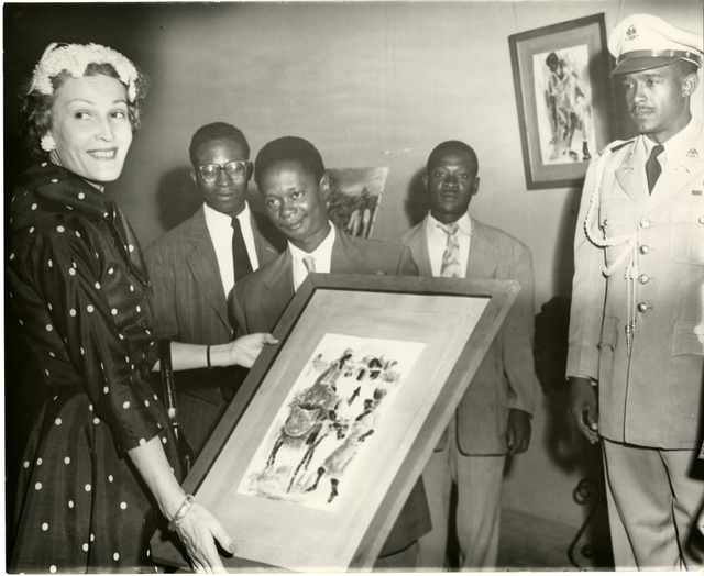 Pat Nixon examines a painting depicting Haitian women during Vice President Richard Nixon's visit to Haiti