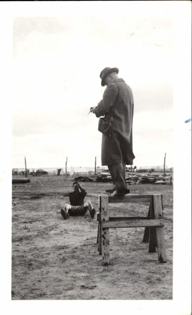 Man Taking Picture of Man Standing on Sawhorse