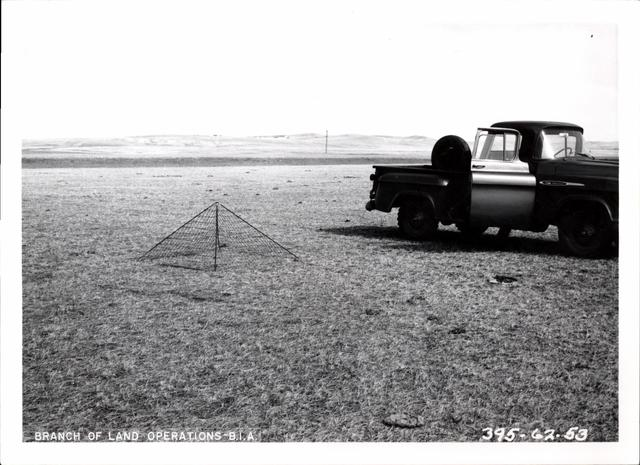 Truck and Triangular Cage in Field