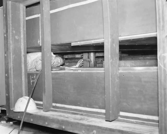 "184-inch cyclotron, workman jacking up upper auxilary coil. Photo taken 3/08/1956. 184""-1421 Principal Investigator/Project: Analog Conversion Project"