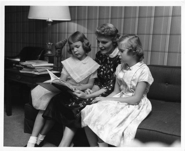 Pat Nixon reads to her daughters Julie and Tricia Nixon from a children's book