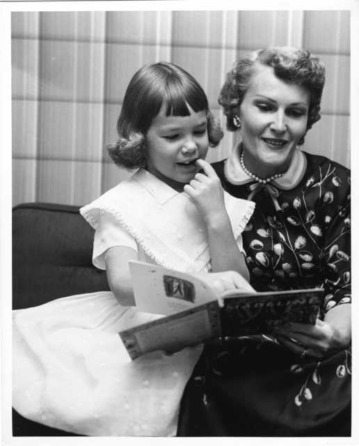 Pat Nixon reads to Julie Nixon from a children's book