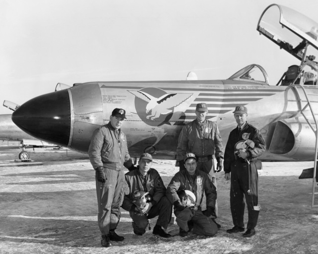 """U.S. Air Force personnel assigned to the 119th Fighter Wing""""Happy Hooligans"""", North Dakota Air National Guard, pose for a photograph standing in front of a F-94 A/C Starfire aircraft at Hector Field, North Dakota. The""""Happy Hooligan""""pilots flew the F-94 A/C Starfire aircraft from 1954-to-1960. Pictured standing left-to-right are: Marshall Johnson; Thor Hertsgaard; and Duane""""Pappy""""Larson. Kneeling left is Alexander P. Macdonald.  The person kneeling on the right is unknown. (A3604) (U.S. Air Force PHOTO) (Released)"""