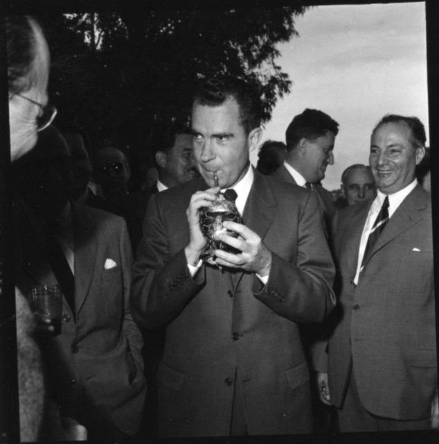 Vice President Richard Nixon drinks yerba mate from a mate gourd at a barbeque luncheon held at the residence of Luis Batlle Berres in Montevideo, Uruguay