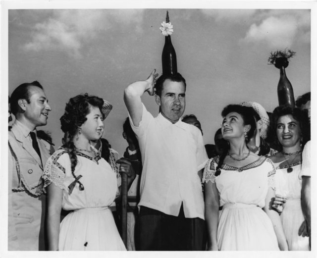 Vice President Richard Nixon, while attending a barbeque luncheon in Paraguay, balances a bottle on his head as he participates in a Paraguayan bottle dance