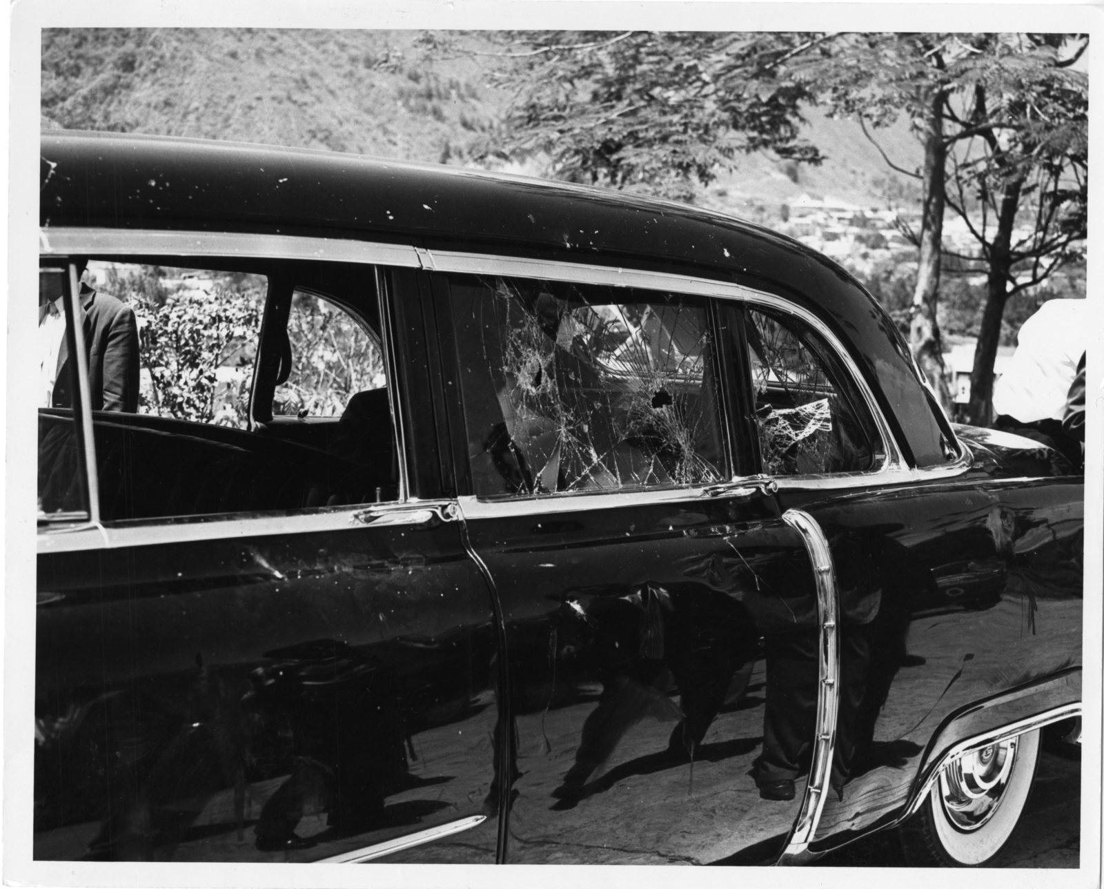 An automobile that has sustained damage following a mob attack in Caracas, Venezuela, targeting Vice President Richard Nixon. Close-up of shattered windows