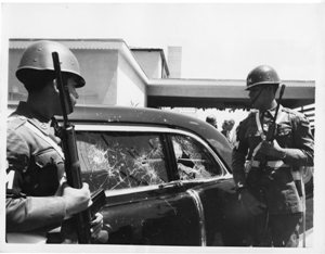 Armed guards look over an automobile that has sustained damage following a mob attack in Caracas, targeting Richard Nixon. Close-up of shattered windows