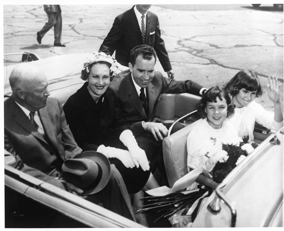 Vice President Richard Nixon rides in the back seat of an automobile with Dwight Eisenhower and Pat Nixon upon the Nixons' return from South America