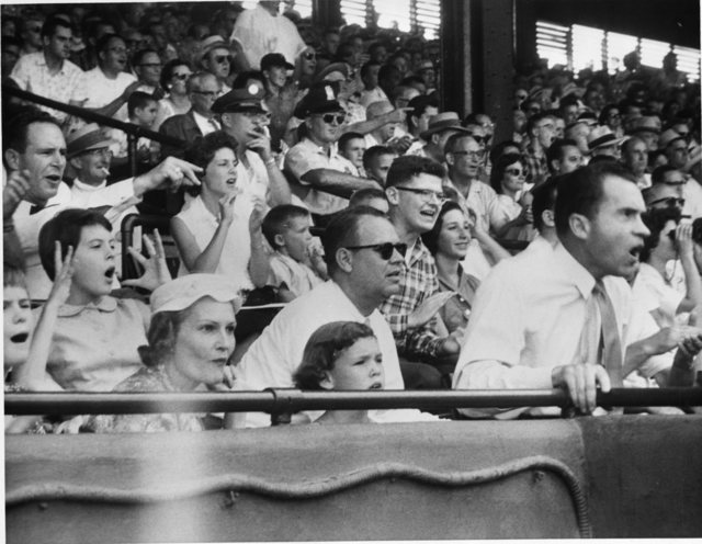 Richard, Pat, Tricia, and Julie Nixon cheering at a baseball game at Griffith Stadium