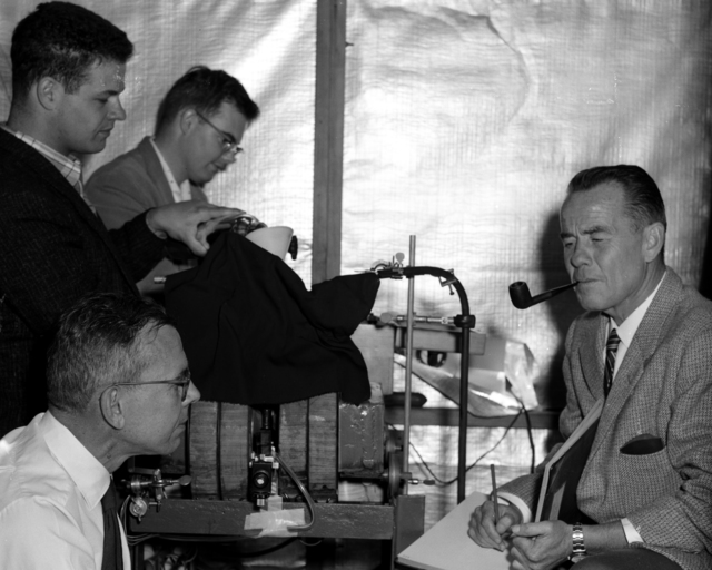 Isolation of californium (in visible amounts). Inside a fabricated tepee on the roof of the Chemistry Building, the chemists perform their experiment. Left to right: Ray Gatti. (standing). and Llad Phillips (seated) with Burris Cunningham and Stanley Thompson, taken September 1958. Morgue 1958-62 (P-1) [Photographer: Donald Cooksey]