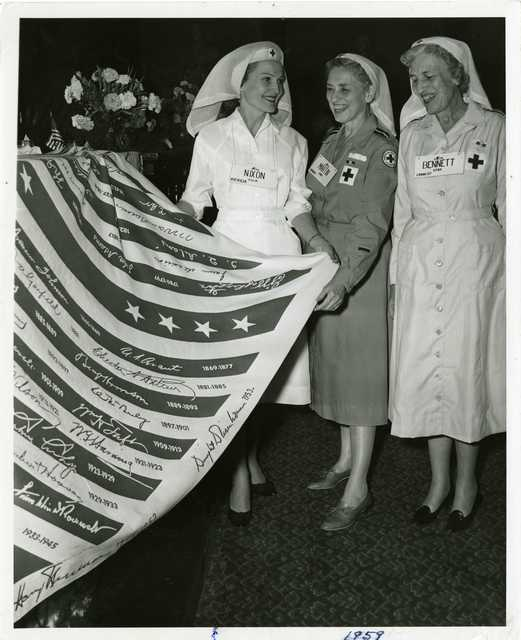 Pat Nixon, Dorris Martin, and Frances Bennett, wearing Red Cross uniforms, hold a commemorative item listing U.S. presidents and their terms