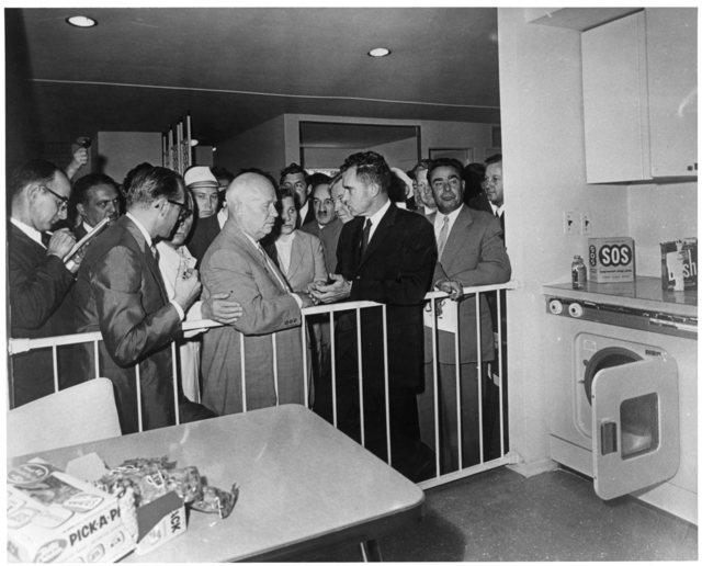 Richard Nixon and  Nikita Khrushchev debate at the American Exhibition in Moscow. They stand in front of a reproduction American kitchen during the exchange