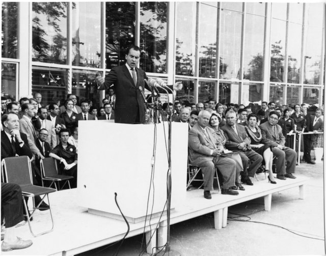 Richard Nixon speaks at the opening of the American Exhibition in Moscow's Sokolniki Park. Nikita Khrushchev, Pat Nixon, and others sit in chairs beside a podium