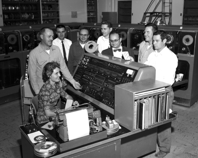 The last univac run was performed by Jonnie Daw (Computation Division), seated. Left to right, standing: Stan Helmeci (Computation Division); Ed Lafranchi, Cedric Eastburn, and Marv Lehman (Electronics Engineering); Sidney Fernbach (Head of Computation and Theoretical Divisions); Pierre Noyes (Theoretical Division); and John Hudson (Computation Division), taken November 1959. Morgue 1959-115 (P-1) [Photographer: Donald Cooksey]