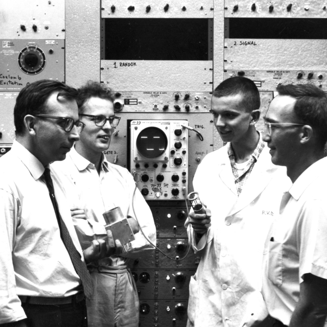 The experimenters of the coulomb-excitation studies gather in front of an oscilloscope. Left to right: Jerry Igo (physicist), Bent Elbek (physicist), Dick Brower (graduate student, chemistry), and Dick Diamond (chemist), taken October 1959. Morgue 1959-59 (P-1) [Photographer: Donald Cooksey]