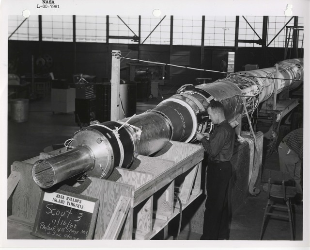 Photograph of a Scientist Examining a Rocket inside a Warehouse at the Langley Research Center in Hampton, Virginia