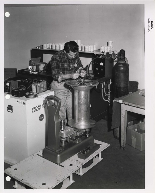 Photograph of a Scientist Examining a Rocket Part Related Project Beacon, at the Langley Research Center in Hampton, Virginia
