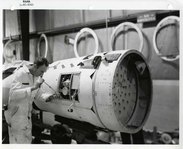Photograph of a Scientist Examining and Adjusting a Rocket Part inside of a Warehouse