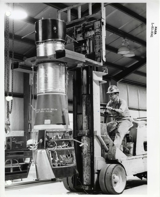 Photograph of a Scientist Operating a Vehicle to Transport a Rocket Part inside of a Warehouse