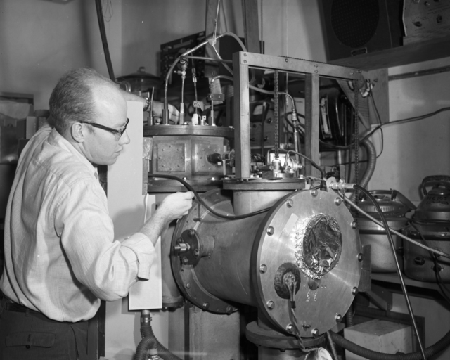 Working rapidly, physicist Vern Ehlers adjusts the atomic-beam machine, which will give him data on nuclear and atomic spin of gallium-70. (Helicopter aids Berkeley physicists working with fast-decaying elements). Taken, January 1960. Morgue 1960-36 (P-2) [Photographer: Donald Cooksey]