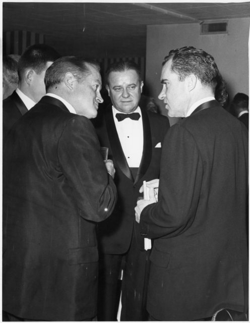 Richard Nixon and Bob Hope face one another in profile at the National Press Club Inaugural Dinner. Ed Edstrom looks onward