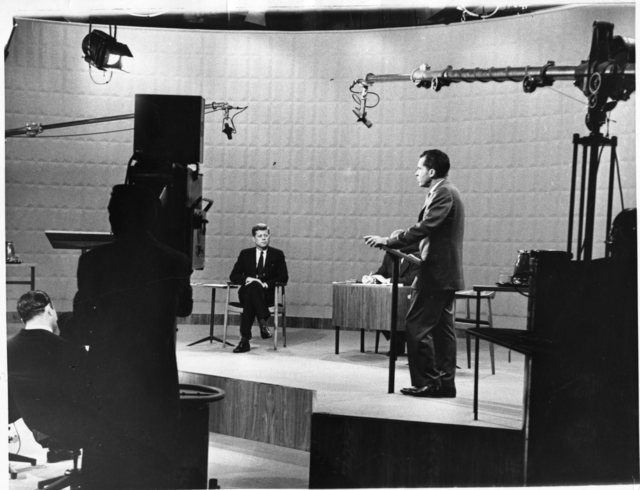 Richard Nixon and John F. Kennedy debate in Chicago while being televised