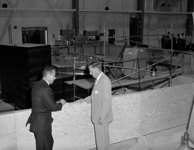 Discussing the cyclotron magnet (seen in the background) are Dr. Elmer Kelly, physicist in charge of the 88-inch cyclotron and Warren Dexter, who is electrical coordinator for the cyclotron project. Morgue 1960-102 (P-4) [Photographer: Donald Cooksey]