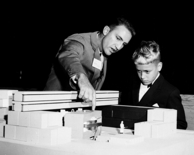 Ken Mirk left pointing at model of the new cyclotron with Chris Atterling, son of visiting scientist Hugo Atterling of Sweden looking on, December 1960. Open House at Bldg. 88. Morgue 1960-102 (P-1) [Photographer: Donald Cooksey]