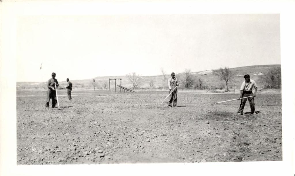 Men Hoeing, Playground Equipment in Background