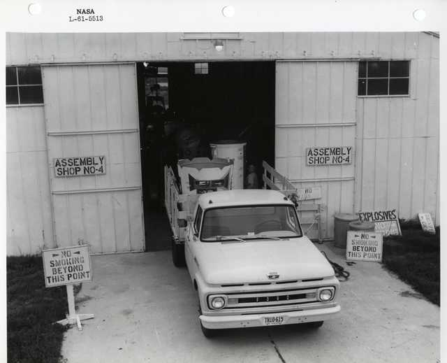 Photograph of a Ford Truck with Rocket Parts in the Truck Bed Parked in from of Assembly Shop No-4