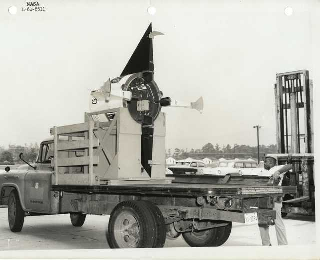 Photograph of an Man Securing a Rocket Part in the Bed of an Official Vehicle