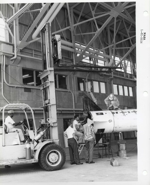 Photograph of Five Men Attempting to Secure a Rocket Part to a Vehicle for Transport