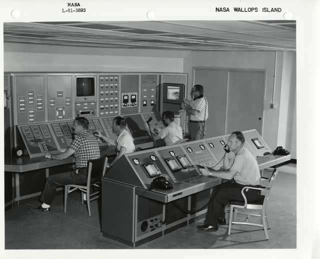 Photograph of Five Scientists Sitting at a Control Atation Answering Telephones at Wallops Island Launch Area in Virginia
