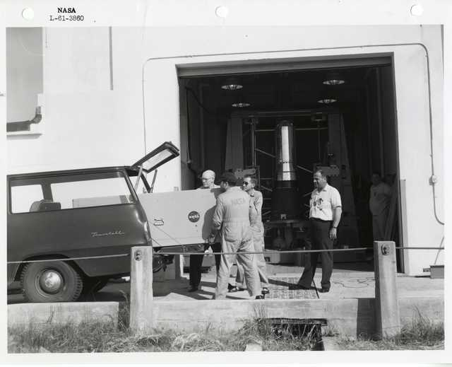 Photograph of Men Loading a Crate into the Back of a Car