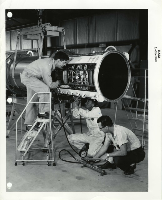 Photograph of three Scientists Examining and Testing a Rocket Part in a Warehouse