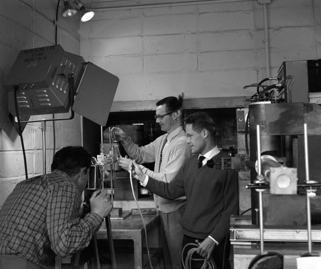 A moving picture is made for the National Aeronautics and Space Agency on the experimental work being done in bio-organic chemistry. The cameraman (left) photographs Dr. Christof Palm (right) and William Everette of the Linac Group (center), taken February 1961. Morgue 1961-44 (P-1) [Photographer: Donald Cooksey]