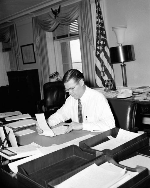 Secretary of Defense Robert S. McNamara works at his desk in the Pentagon