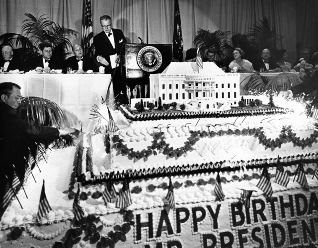 President John F. Kennedy, Seated at a Table with Speaker of the House Sam Rayburn, Democratic National Committee Chairman John Bailey, and Attorney General Robert F. Kennedy, Looks at his Birthday Cake at the President's Birthday Party at the National Guard Armory in Washington