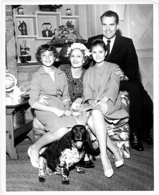Living room portrait of Richard Nixon, Pat Nixon, Tricia Nixon, and Julie Nixon -- including the family's pet dog Checkers