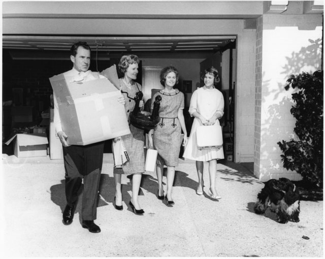 Richard Nixon and family emerge from a garage holding household items