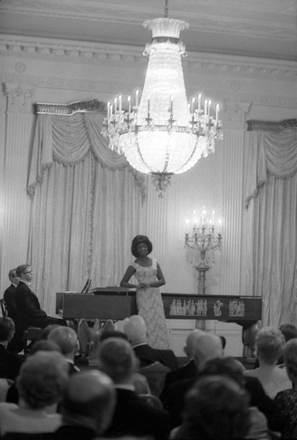 Mezzo-Soprano Opera Singer Grace Bumbry Stands at the Piano in the East Room before Performing for Guests at a Dinner in honor of Vice President Lyndon B. Johnson, Speaker of the House of Representatives John W. McCormack, and Supreme Court Chief Justice Earl Warren